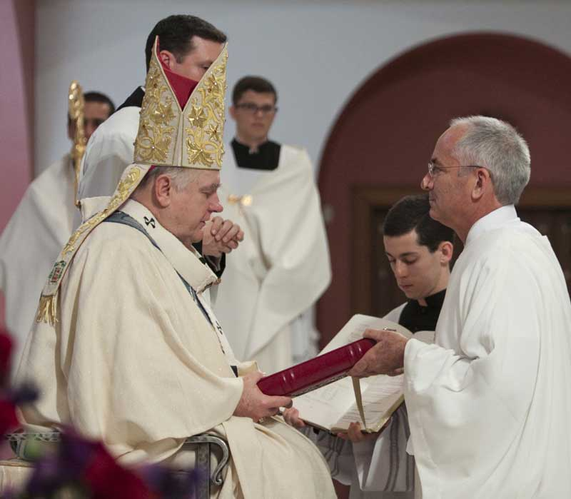 Deacon George Labelle receives the Book of the Gospels from Archbishop Thomas Wenski. Photo: Ana Rodriguez-Soto | Florida Catholic